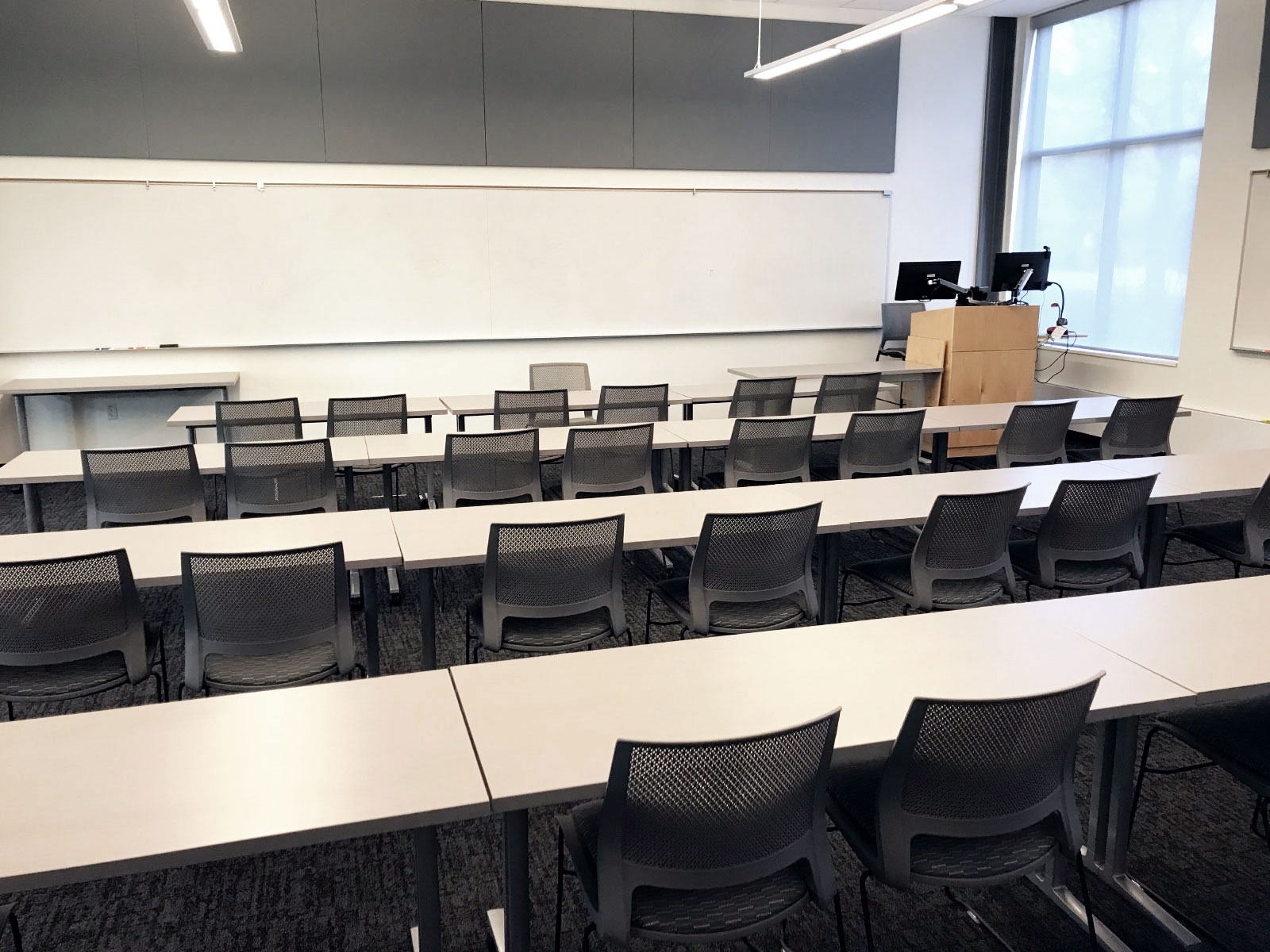 Rows of chairs and tables with a podium in front of a whiteboard in Harmony Campus classroom