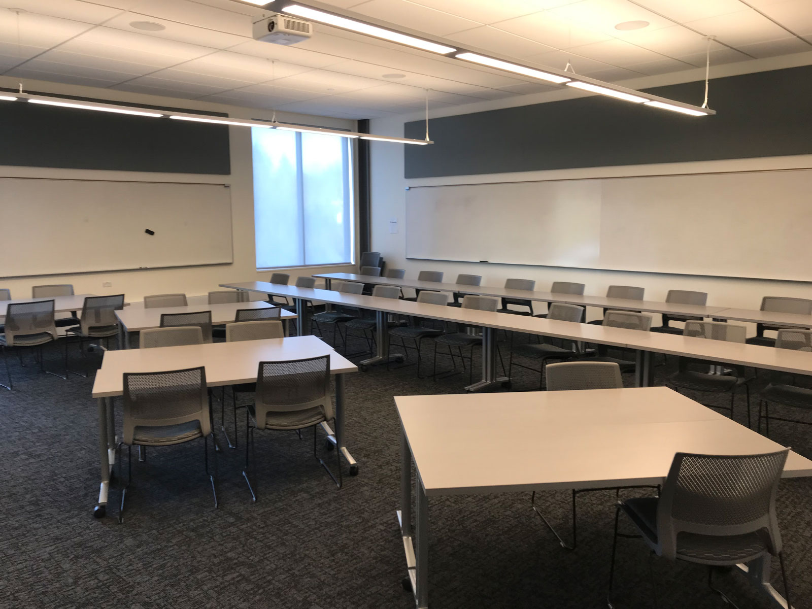 Two rows of tables and chairs in front of several separate tables in a Harmony campus classroom