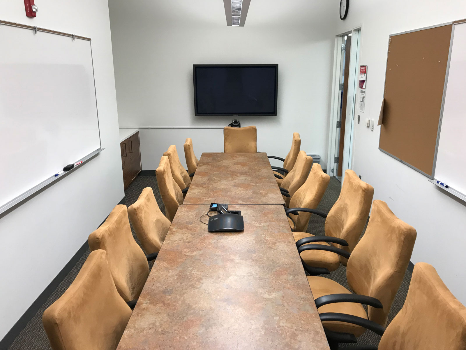 Two rows of chairs and table in a small Harmony campus conference room