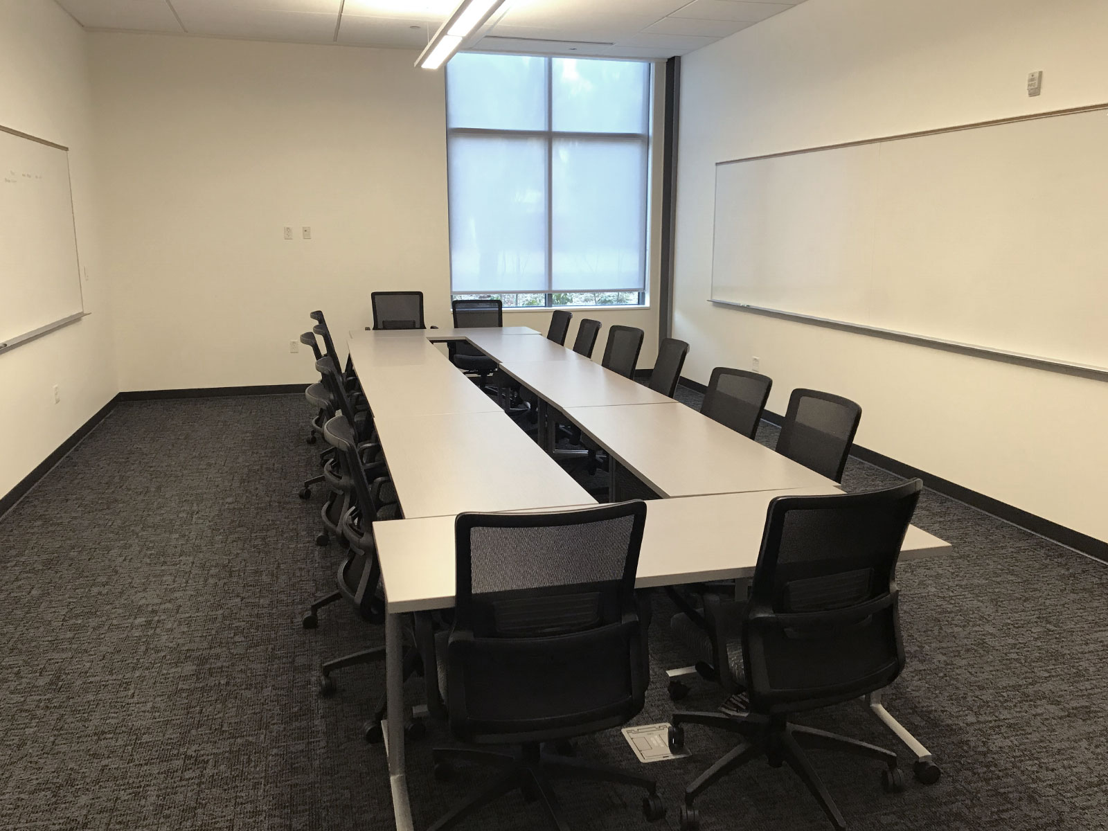Two rows of chairs and tables in a large Harmony campus conference room