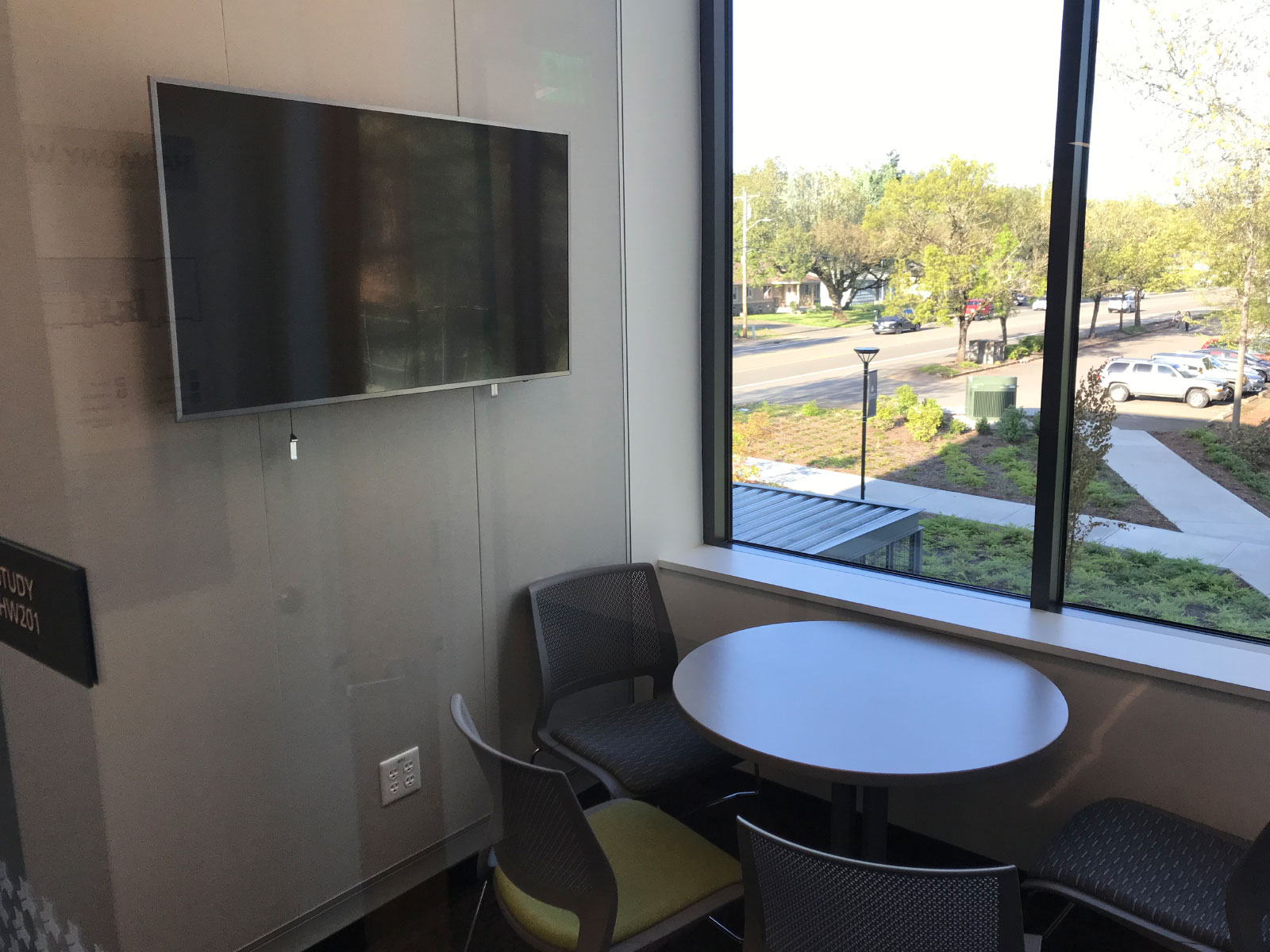 A TV screen in front of a window and small table with chairs in the Harmony campus conference room