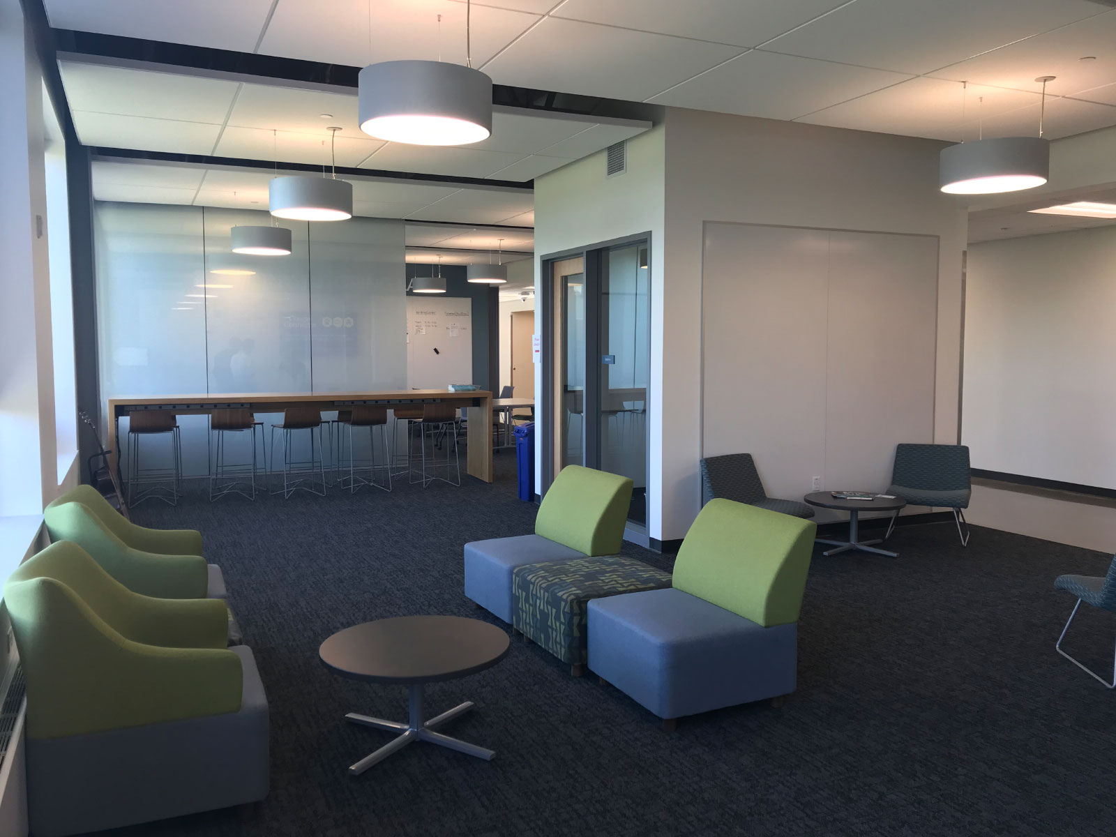 Various small meeting spaces with green and blue chairs in the Harmony campus lobby