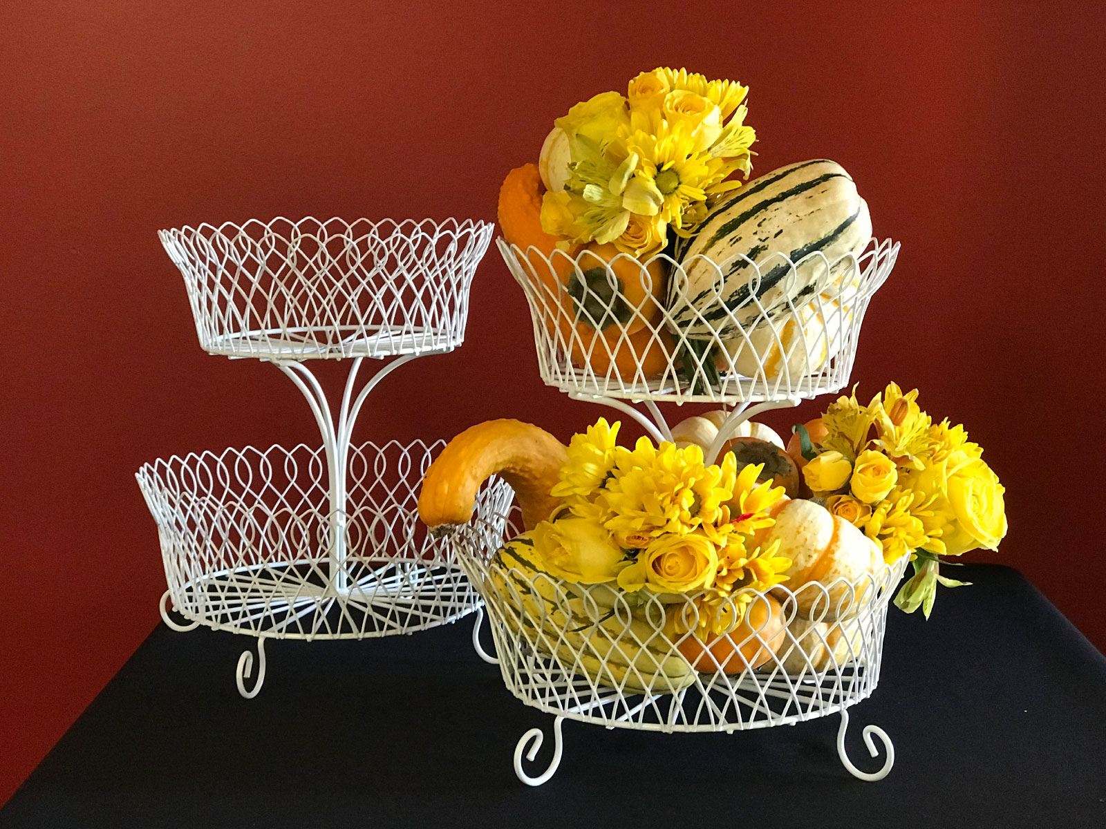 Several wax vegetable centerpieces including squash and pumpkins with flowers in white baskets