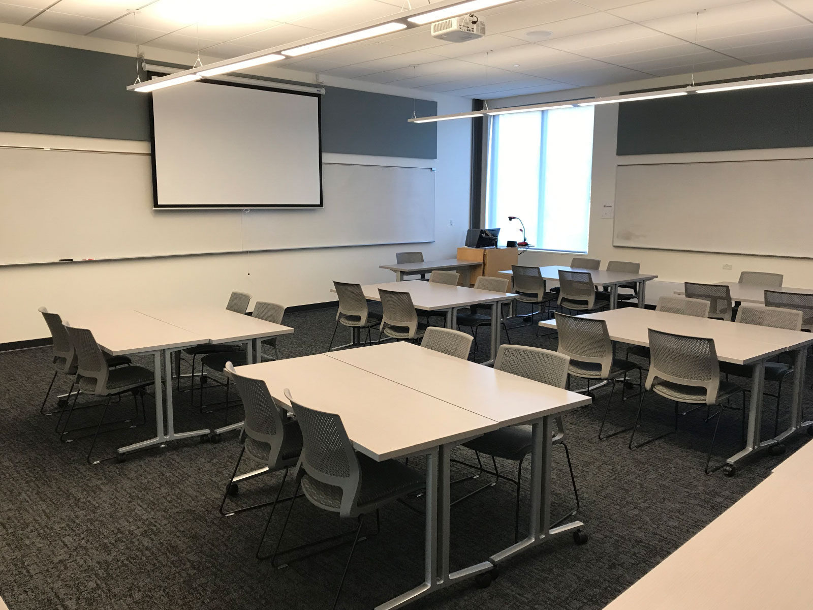 Several tables with chairs in front of a projector screen in a Oregon City campus classroom