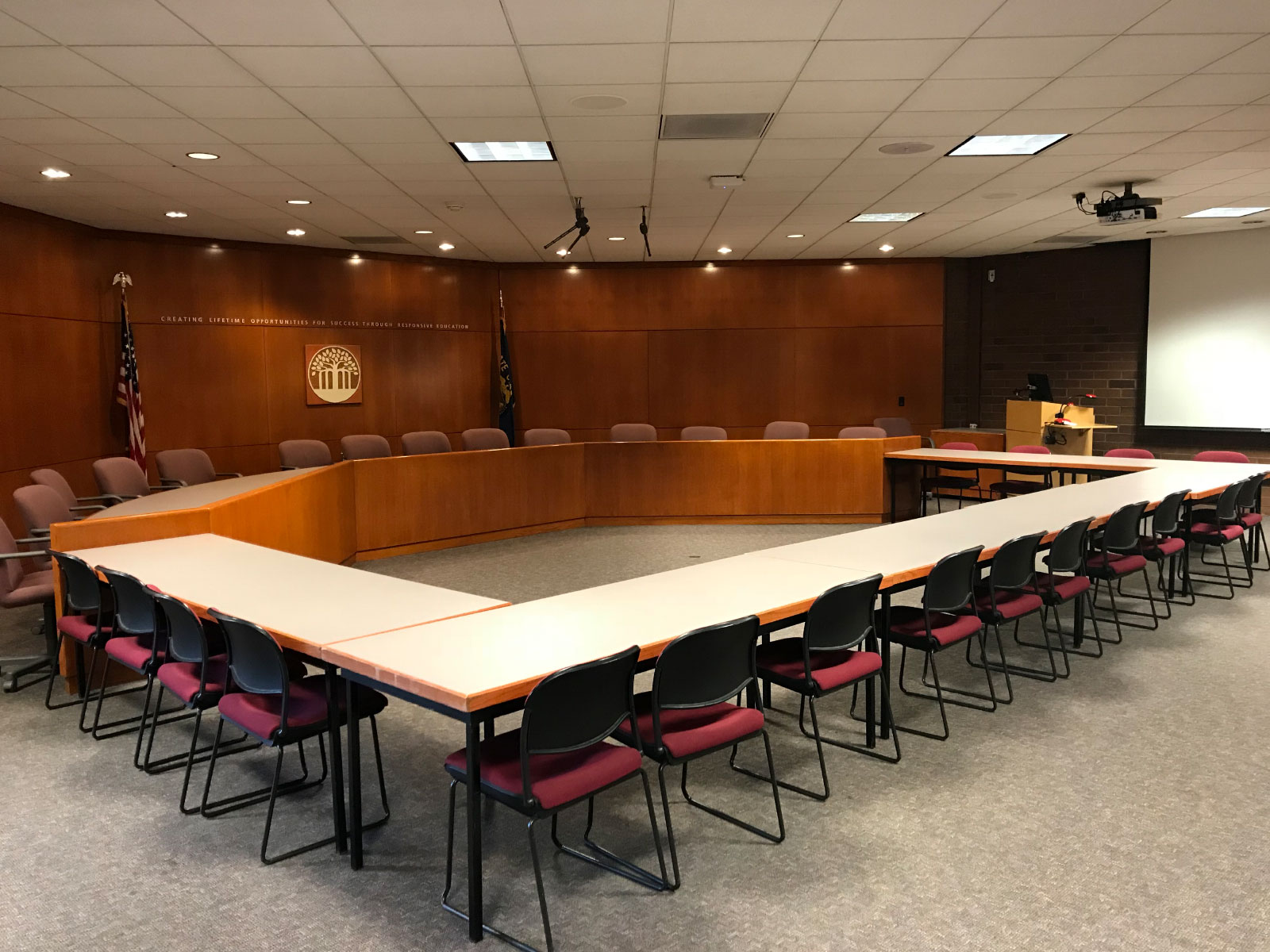 The large Community Center Board Room in room 127 at the Oregon City campus, with dozens of seats in an angular circle, with podium and projector