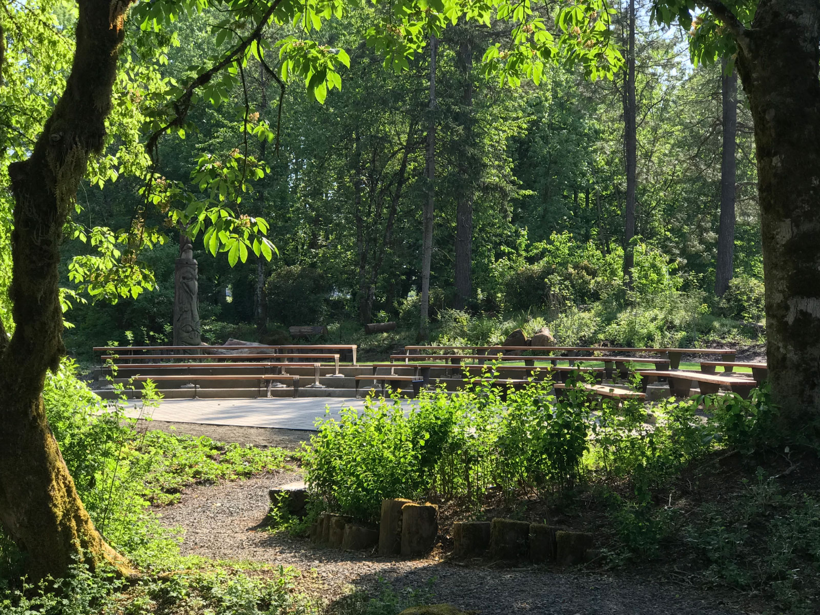 Trees, grass and a gravel path in front of the ELC amphitheater with rows of seats, at the Oregon City campus