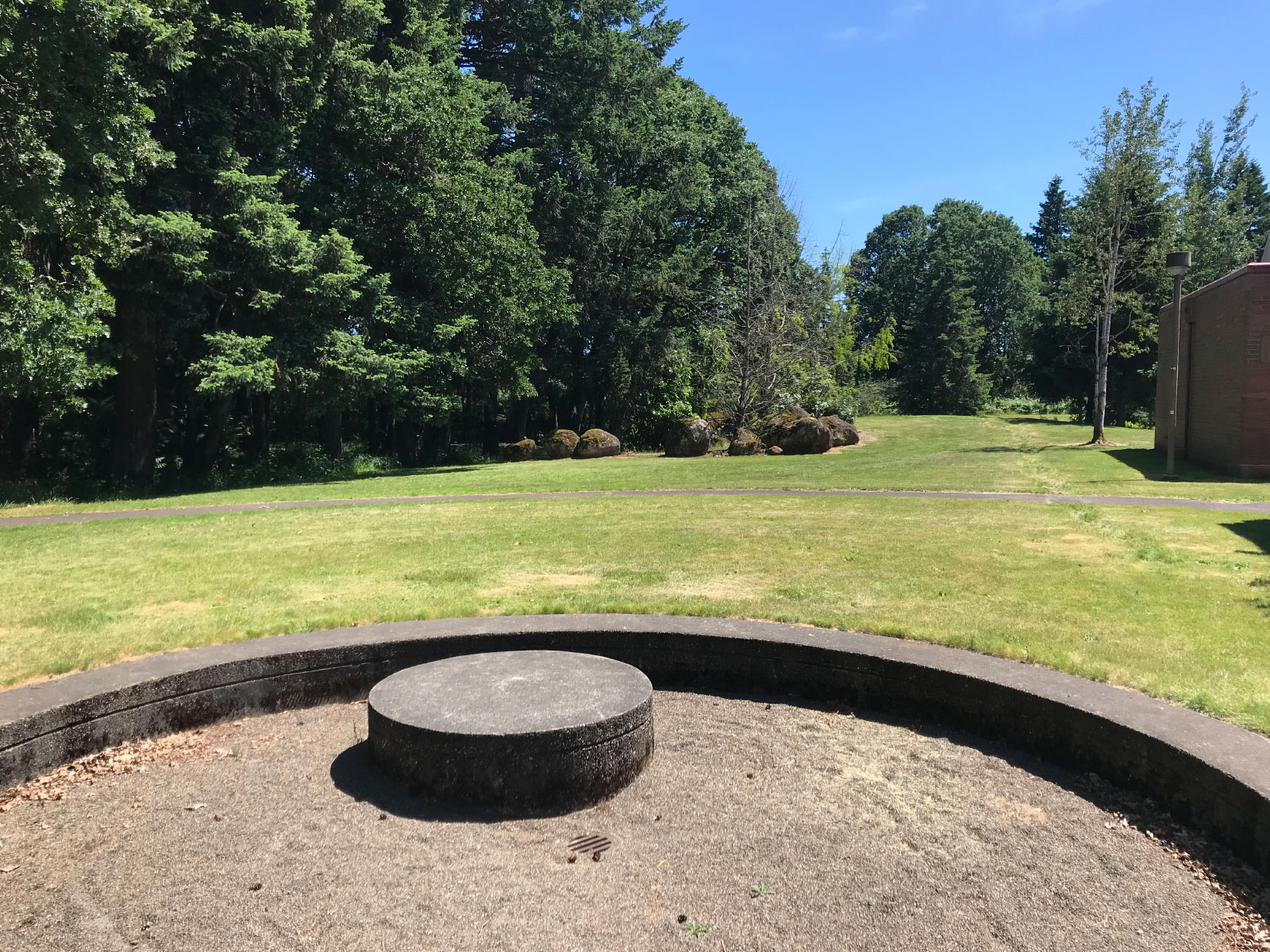 A circular, stone structure pit with sand in an open field on the Oregon City campus