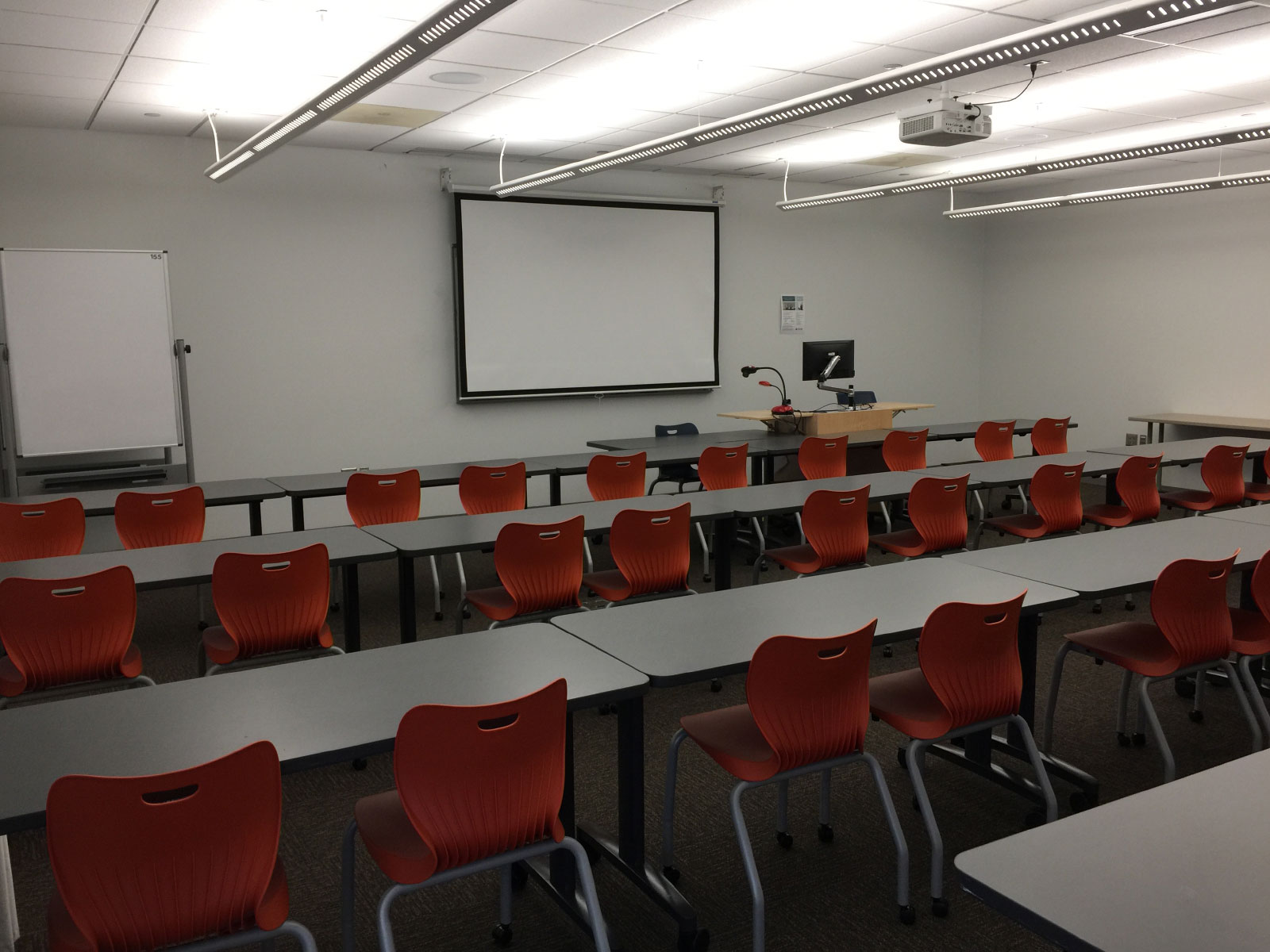 Rows of orange chairs and tables in front of a podium and projector in classroom W155 on the WIlsonville campus