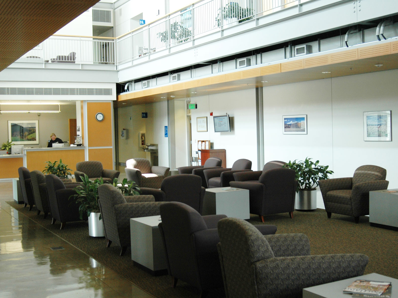 Displays, the front desk and rows of chairs in the lobby and commons gallery of the Wilsonville campus