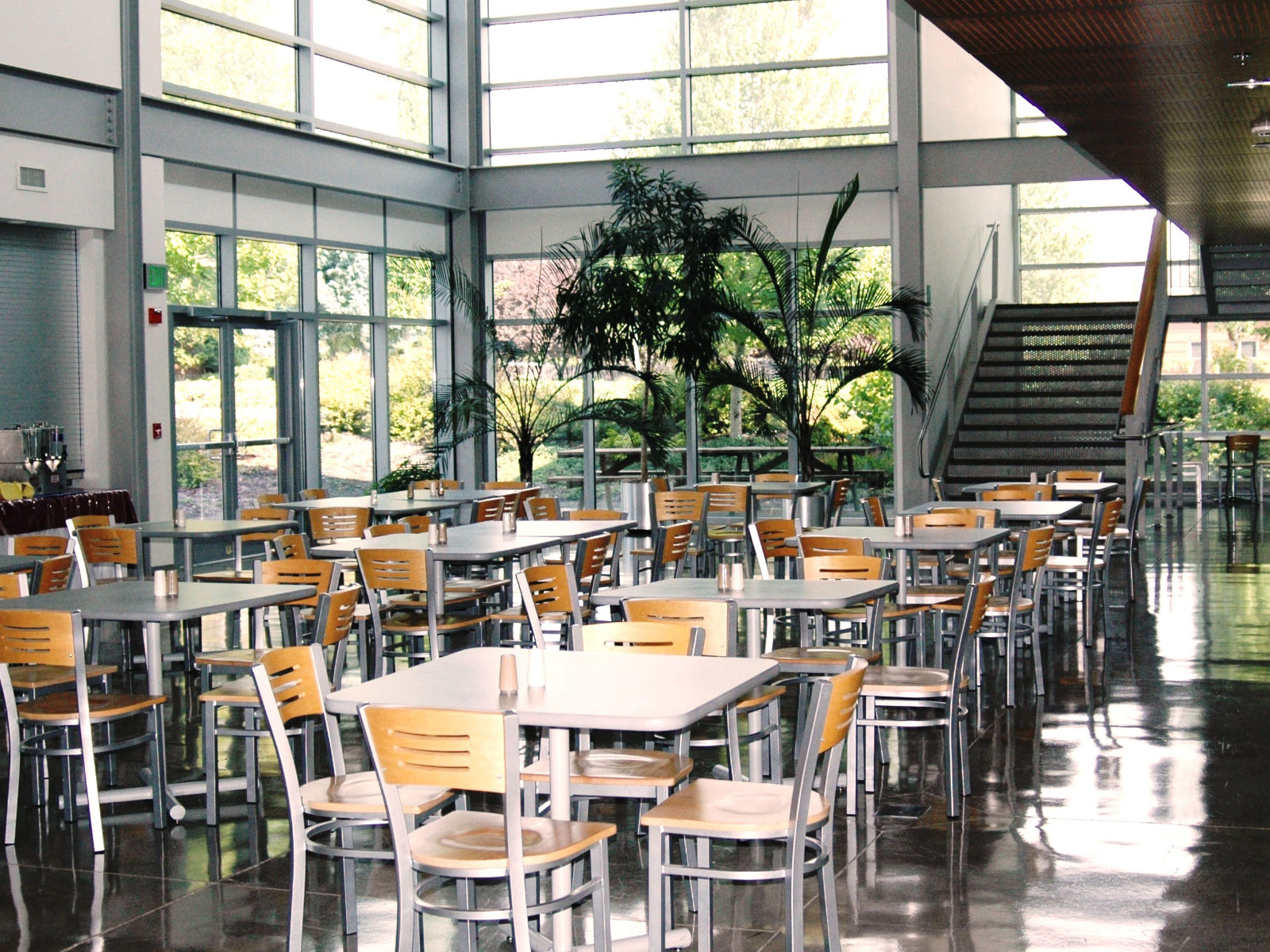 Rows of tables with chairs in the open commons area next to a set of stairs on the Wilsonville campus