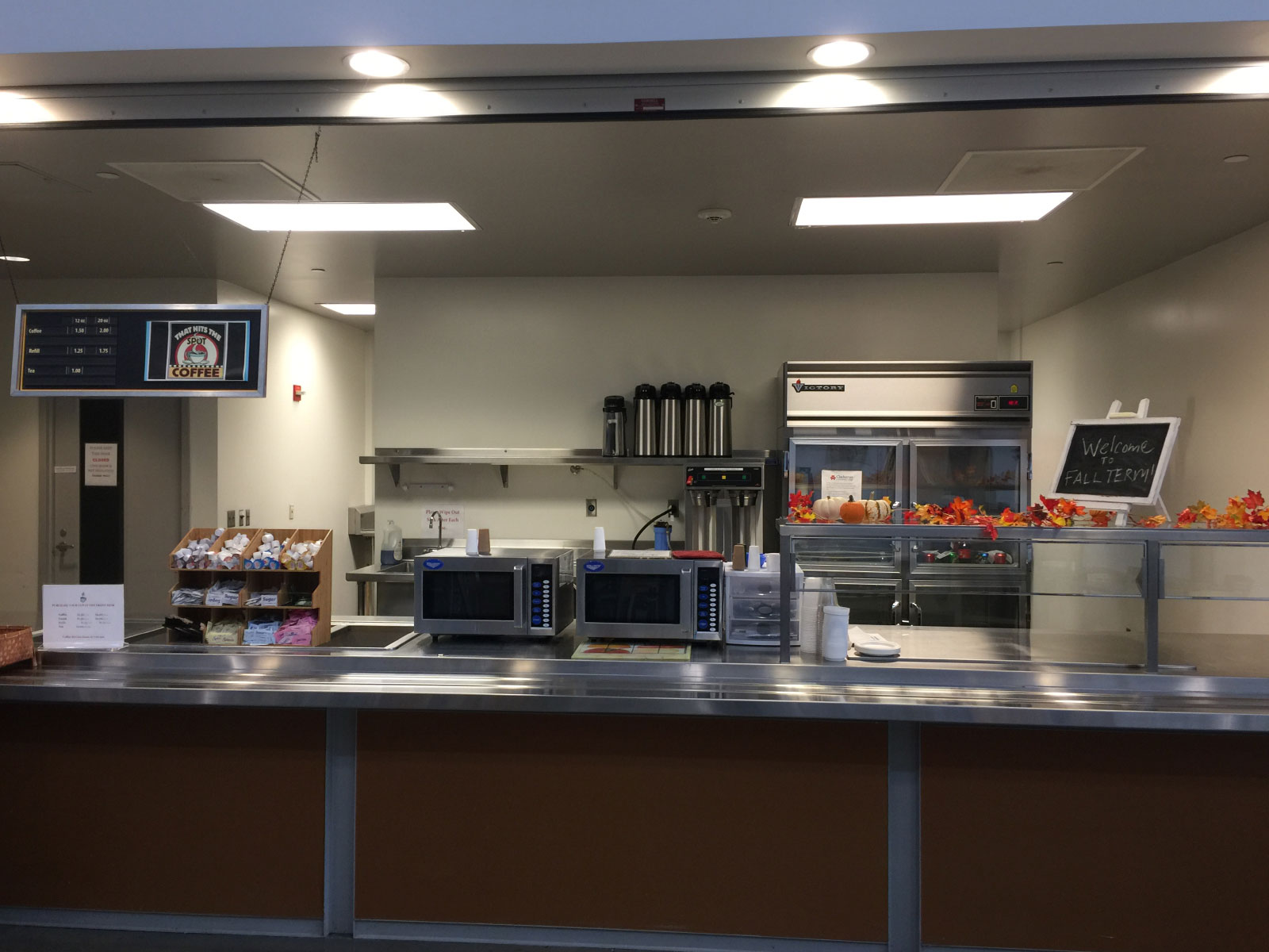 The front of the kitchen area with microwaves, refridgerator, counter and displays of the Wilsonville campus
