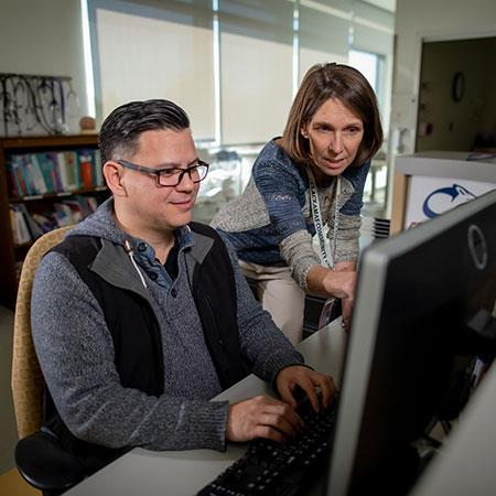 Instructor points to computer monitor as student looks on