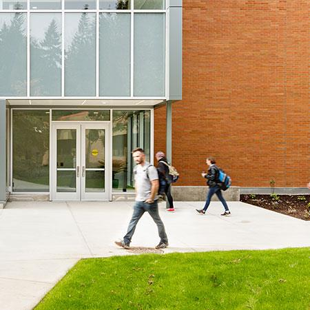 students walk in front of campus building