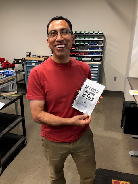 Eduardo with the metal-cover book labelled Get Into Heavy Metals